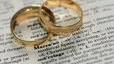 Two gold wedding rings rest on an open dictionary page