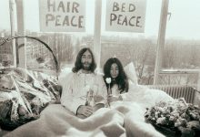 """Black and white photo shows two hippies in bed together beneath signs reading """"HAIR PEACE"""" and """"BED PEACE."""""""