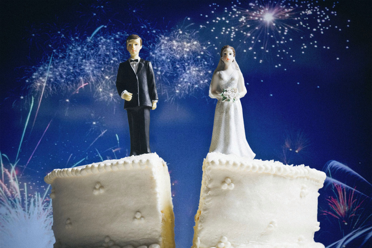 wedding cake split down the center, bride and groom cake toppers stand on either side. fireworks in the background.